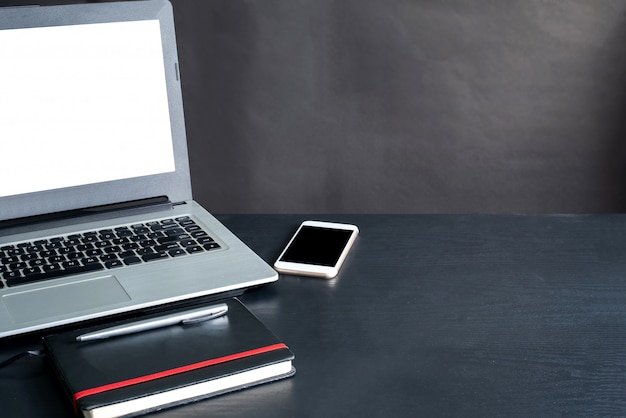 Laptop, smartphone, notizbuch, stift, auf schwarzem holztisch mit schwarzem hintergrund