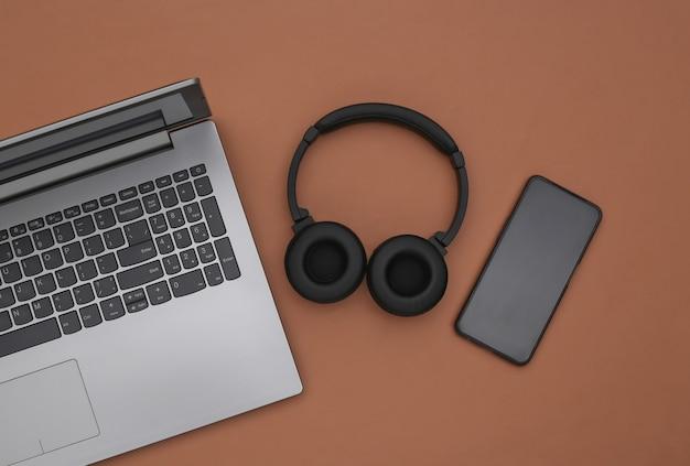 Laptop, smartphone und drahtlose stereo-kopfhörer auf braunem hintergrund. ansicht von oben. flach legen