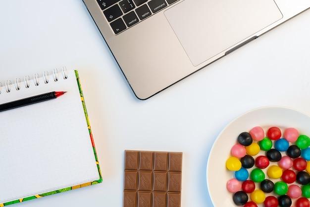 Laptop, süßigkeiten und arbeitsheft mit tafel schokolade und kaffee am arbeitsplatz.