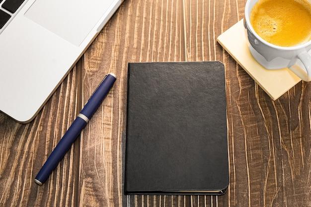 Laptop-tagebuch und kaffeetasse auf dem schreibtisch oder auf dem holztisch draufsicht mit kopierschlitz für design