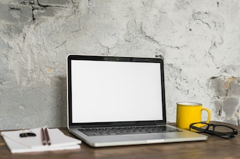 Laptop; Tasse; Brille und Notizblock auf Schreibtisch aus Holz