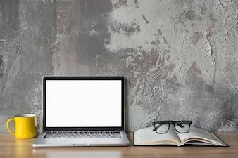 Laptop; Tasse; Buch und Brille auf hölzernen Schreibtisch vor der alten Mauer