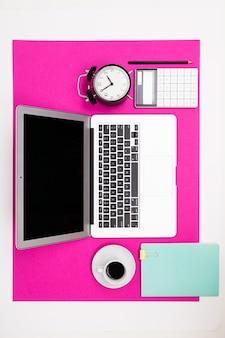 Laptop, tasse, uhr, notizbuch liegen an einer rosa wand