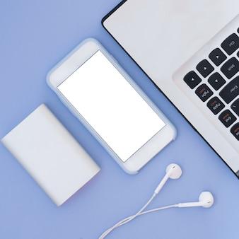 Laptop, telefon, kopfhörer und power bank auf blauem grund. flat lay komposition und platz für text. draufsicht.