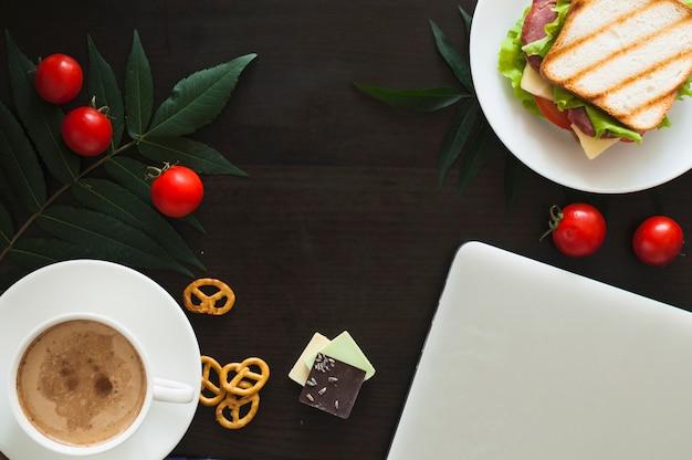 Laptop; tomaten; sandwich; schokoladenstücke; brezeln und kaffeetasse auf schwarzem hintergrund