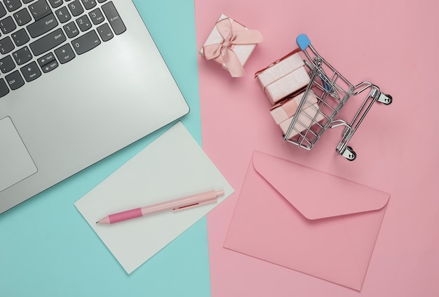 Laptop, umschlag mit brief und stift, schachteln mit geschenken und einkaufswagen auf rosa blauem pastellhintergrund. weihnachten, valentinstag, geburtstag. draufsicht