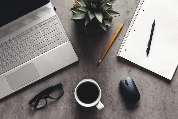 Laptop und buch, kaffee auf grauem hintergrund, draufsicht des schreibtischs auf strukturiertem grauem hintergrund