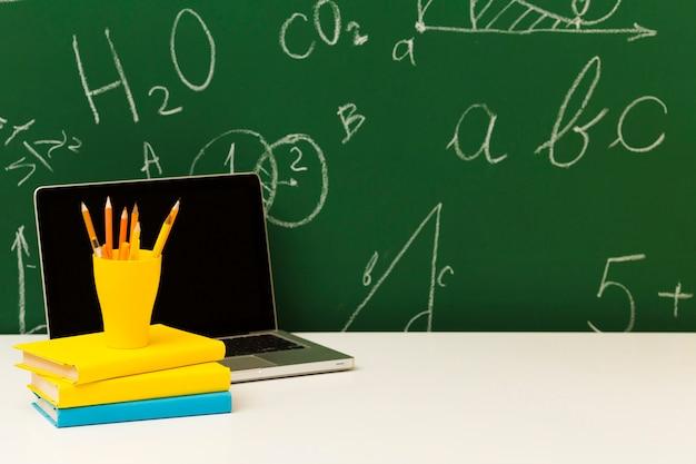 Laptop und bücherstapel auf dem schreibtisch