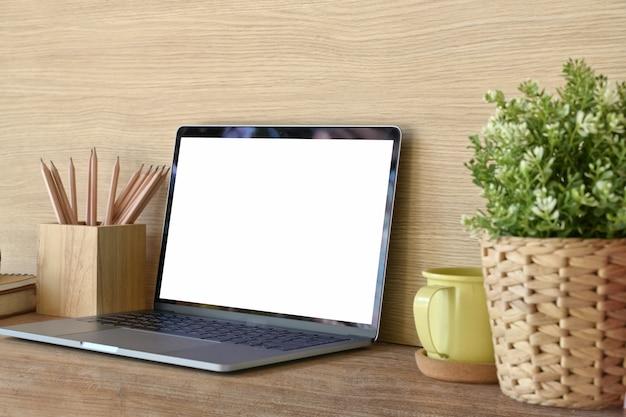 Laptop und büroartikel des leeren bildschirms des modells auf holztisch.