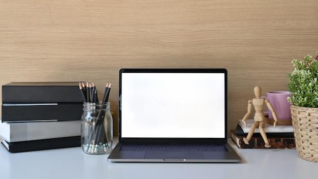 Laptop und büroartikel des leeren bildschirms des modells auf weißer tabelle.