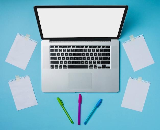 Laptop und bunte stifte mit den papieren festgeklebt mit band auf blauem hintergrund