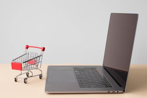 Laptop und ein kleiner wagen für den supermarkt