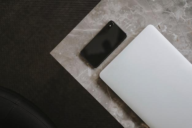 Laptop und ein telefon auf einer marmortabelle