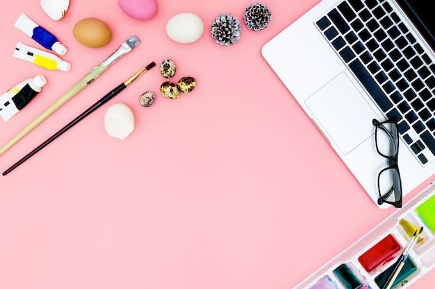 Laptop- und farbensatz, der für ostern auf rosa hintergrund in der flachen lage sich vorbereitet
