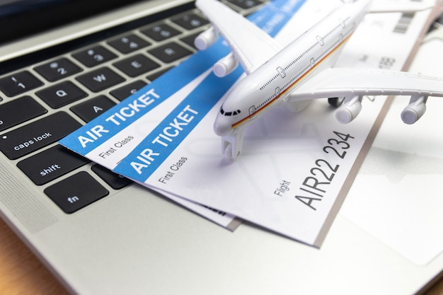 Laptop und flugzeug und geld auf dem tisch. online-ticketbuchungskonzept
