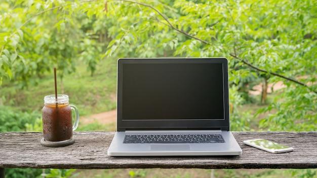 Laptop und gefrorener americano kaffee auf einem holztisch.