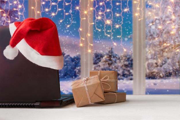 Laptop und geschenke auf dem tisch mit santa claus-hut zu hause mit einem panoramablick