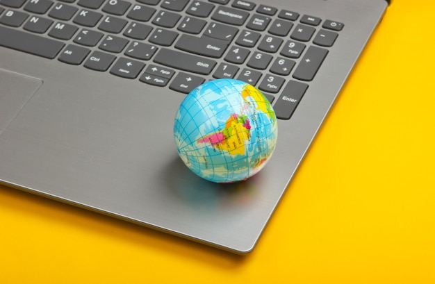 Laptop und globus auf gelber oberfläche