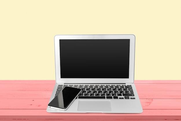 Laptop und handy auf dem tisch
