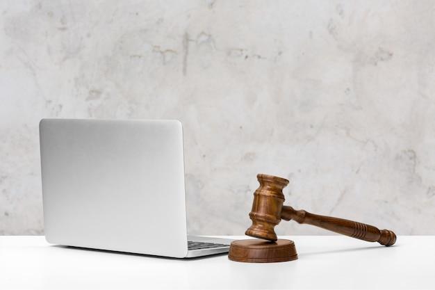 Laptop und holzhammer auf tabelle