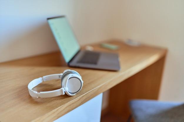 Laptop und kabelloser kopfhörer am arbeitsplatz im home office