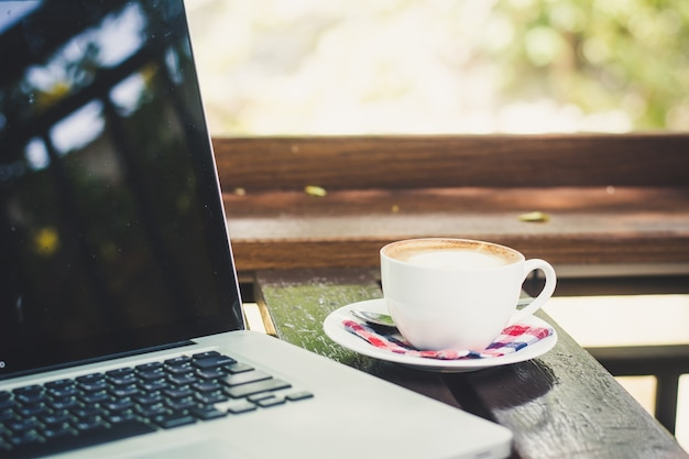 Laptop und kaffeetasse auf tabelle in der kaffeestube
