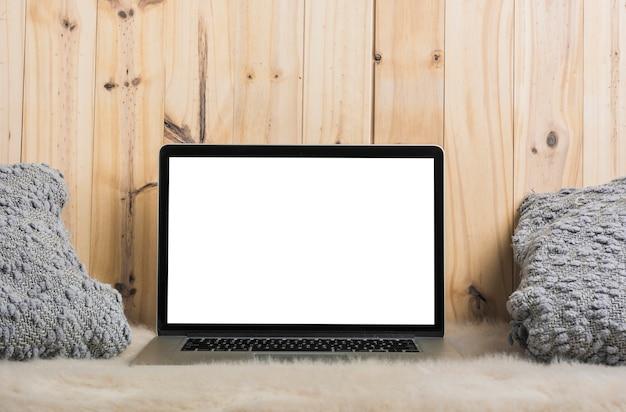 Laptop und kissen auf weichem pelz gegen hölzernen hintergrund