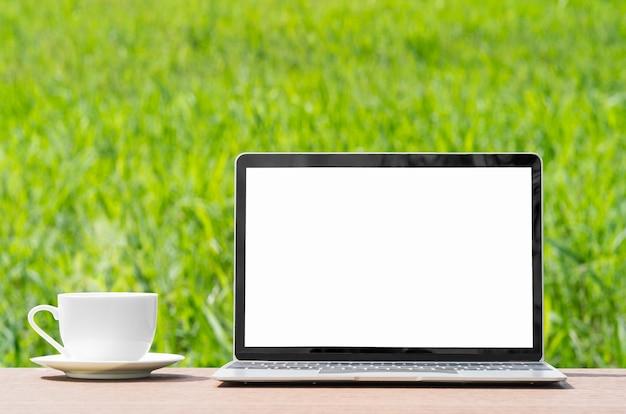 Laptop und kofreie tasse auf grünem grasfeld des holzplankenagenten in der landschaft
