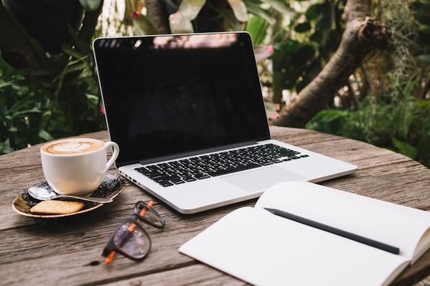 Laptop und notizbuch auf bauholztabelle
