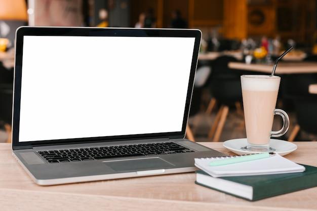 Laptop und notizbuch auf holzoberflächenmodell