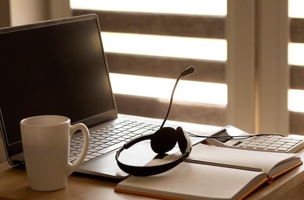 Laptop und notizbuch mit kopfhörern und kaffee, konzeptheimarbeit