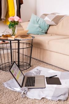 Laptop und pad mit stift auf plaid auf dem boden von bequemer couch mit kissen und kleinem tisch mit buch, tee und rosen in der nähe