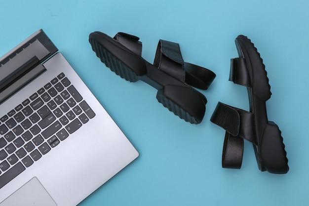 Laptop und sandalen auf blauem hintergrund. ansicht von oben