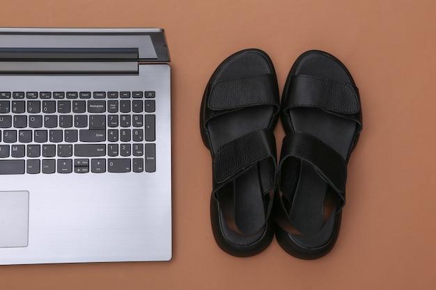 Laptop und sandalen auf braunem hintergrund. ansicht von oben