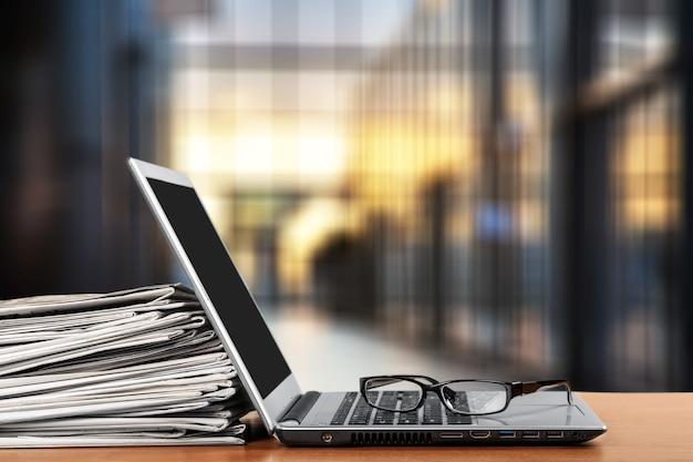Laptop und schwarze brille im hintergrund.