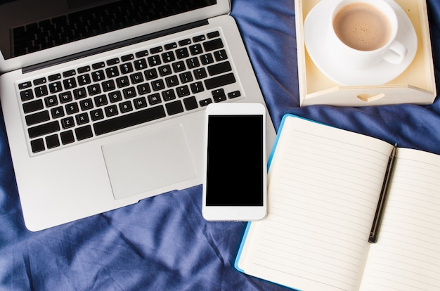 Laptop und smartphone, kaffeetasse und notebook auf dem bett in der morgenzeit. attrappe, lehrmodell, simulation.