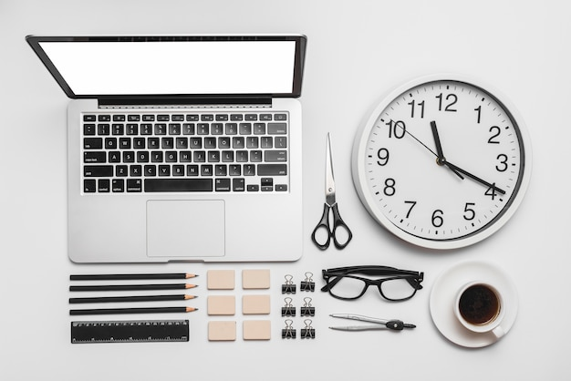 Laptop; wanduhr; tasse kaffee und büromaterial auf weißem hintergrund