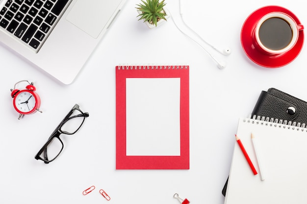 Laptop, wecker, brillen, kaffeetasse, tagebuch, kopfhörer und laptop auf weißem schreibtisch