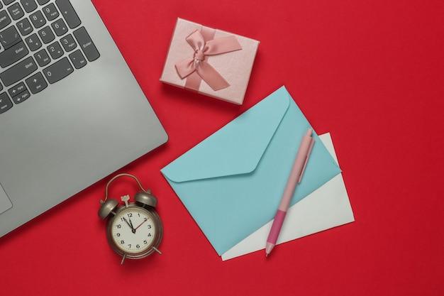 Laptop, wecker, santa briefumschlag, geschenkboxen mit schleife auf rotem hintergrund. 11:55 uhr. neujahr, weihnachtskonzept. draufsicht