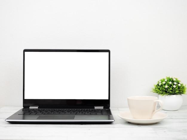 Laptop-weißer bildschirm mit kaffeetasse und vase minimal auf holztisch-arbeitsplatzkonzept