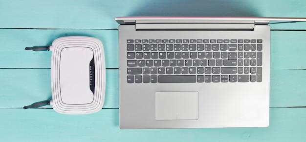 Laptop, wi-fi-router mit antennen auf einem blauen holztisch, draufsicht