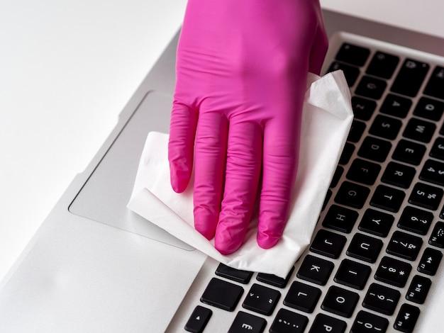 Laptop wird von person mit serviette und op-handschuh desinfiziert