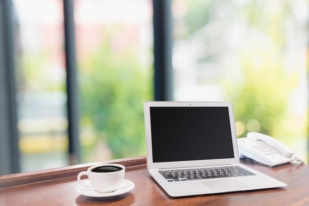 Laptops mit weißer kaffeetasse auf hölzernem schreibtisch
