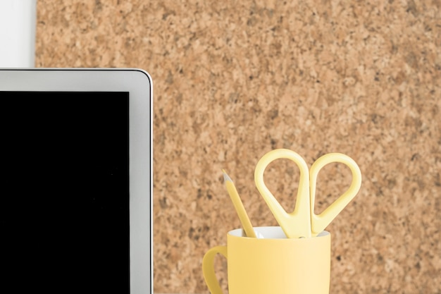 Laptopschirm mit schere und bleistift im becherhalter gegen korkenbrett