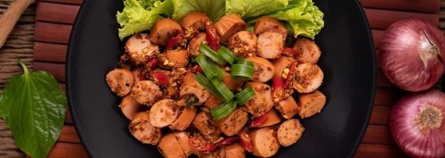 Larb wurst mit chili frühlingszwiebeln und salat in einem schwarzen teller