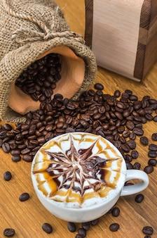 Larte kunst-kaffeetasse auf hölzerner tabelle mit traditionellen kaffeebohnen und schleifer
