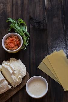 Lasagne backen. italienisches essen. roher lasagnenteig, mozzarella, soße aus bolognese
