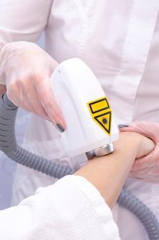 Laser-haarentfernung und kosmetologie. das mädchen entfernt haare am arm mit einem laser. kosmetologie haarentfernung. laser-haarentfernung und kosmetologie. kosmetik- und spa-konzept. vertikales foto