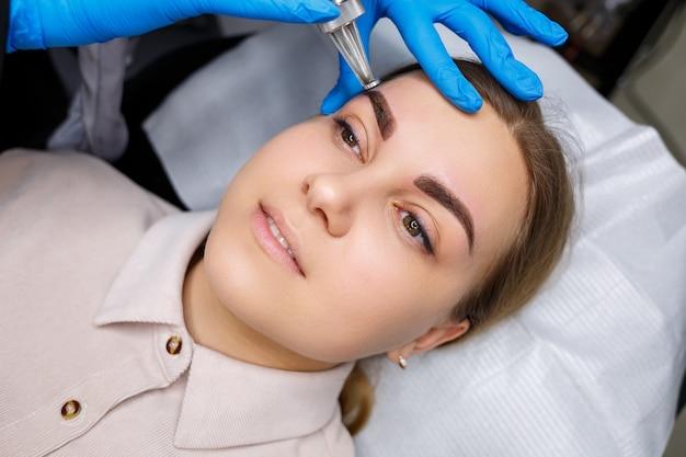 Laserentfernung von permanent make-up im gesicht. nahaufnahme einer jungen frau, die tätowierungskorrektur erhält. korrektur natürlicher unvollkommenheiten im gesicht.