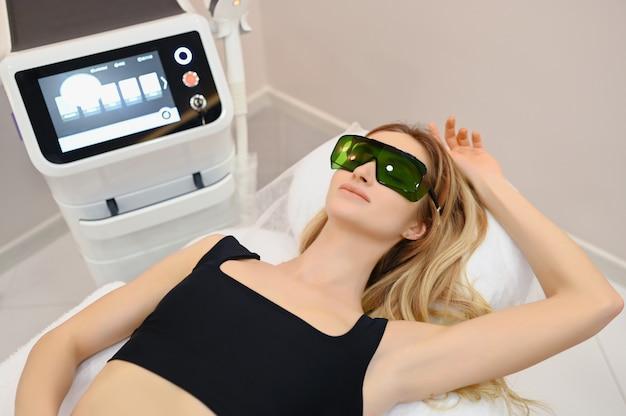 Laserepilation und kosmetologie im schönheitssalon. verfahren zur haarentfernung. konzept für laser-epilation, kosmetologie, spa und haarentfernung. schöne blonde frau, die das haar entfernt auf achselhöhlen erhält